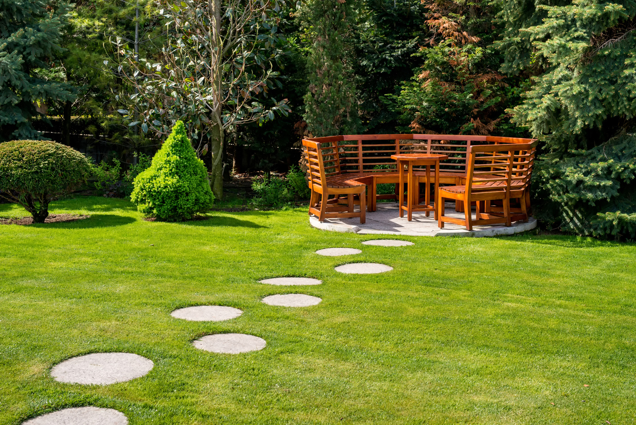 Sunny day in a spring garden with wooden benches
