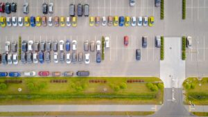 Car parking lot viewed from above, Aerial view. Top view. Lots of vibrant car sunny day, dealership