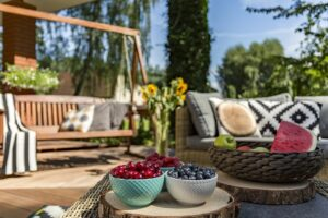 Summer feeling in the house garden with seasonal fruits and wooden furniture